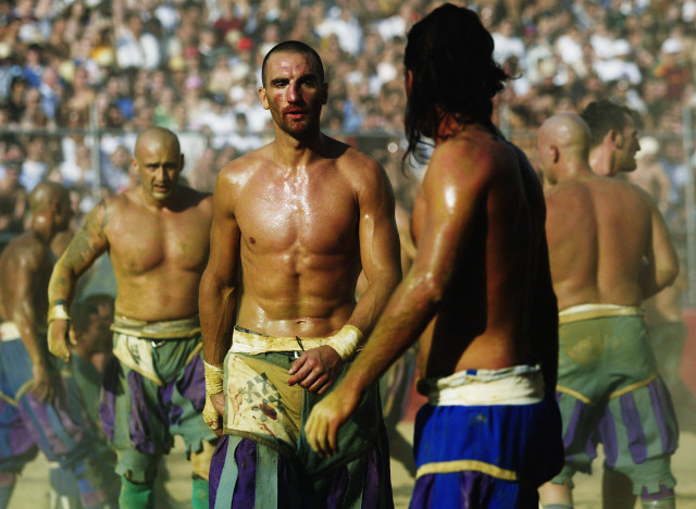 FLORENCE - JUNE 24:  The intense heat and battle shows on the Verdi and Azzurri team members during the Calcio Storico, a medieval football rules event held between four quarters of Florence since 1584 on June 24, 2003 at La Piazza Santa Croce in Florence, Italy.  (Photo by Michael Steele/Getty Images)